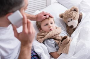 high angle view of daddy talking by smartphone and touching sick son forehead in bedroom